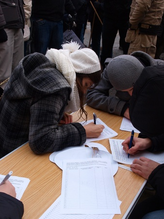 Young Poles protesting against Polish government signing the ACTA (Anti-Counterfeiting Trade Agreement): signing the petition, Lublin, Poland, 26th January 2012.