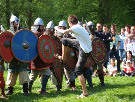 reconstructing: Man trying to break the formation of the medieval knights at the historical reenactment event, Zawieprzyce, Poland, May 6th 2012