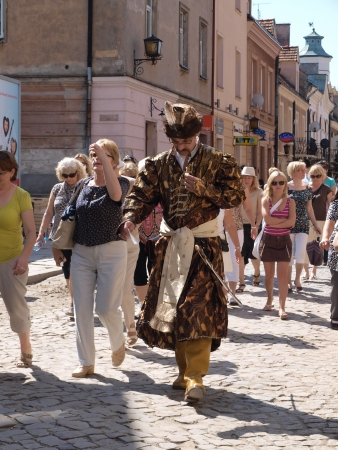 A city guide showing tourists around Sandomierz, Poland in the outfit of the Polish nobleman
