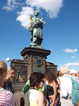 Tourists queuing to touch a relief below statue of St John of Nepomuk, where he was thrown off the Charles Bridge in 1383, brings good luck, Prague, Czech Republic