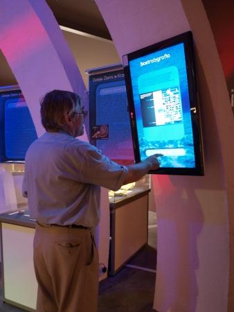 Un turista tocar una pantalla interactiva en el museo multimedia en la mina neolítica de sílex rayado, Krzemionki, Polonia