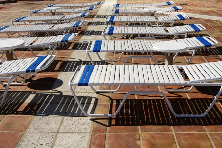 chaise longue on tile cast schadows in a hot day Stock Photo
