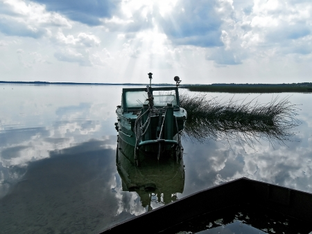 windless: reflection in clear transparent water of the Naroch lake with old launch on shore on a windless day