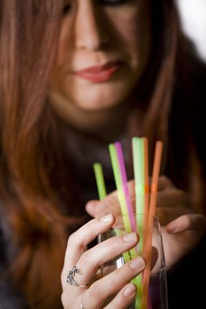 a pretty girl holding a glass full with colorful straws