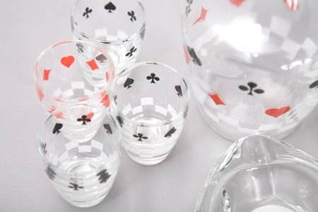 a set of shot glasses and ashtrays with pattern of cards Stock Photo