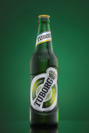 dewed: MINSK, BELARUS-AUGUST 23, 2016. Tuborg glass bottle beer on green background. Editorial
