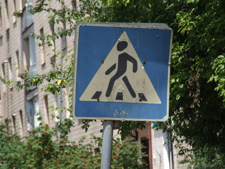 Old road sign of a pedestrian crossing in the city