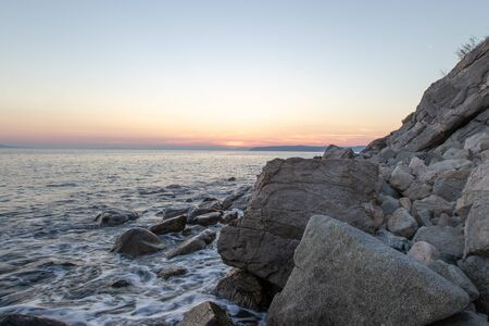 The sea wave hits the stones at sunset near the coast of the Holy Mount Athos