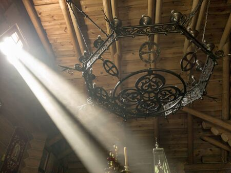 The rays of the sun make their way through the windows and cracks of the Orthodox church on the throne and sacred objects