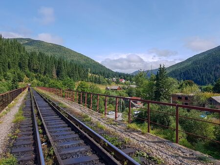Beautiful mountain narrow-gauge railway road, rails in the mountains of the Carpathians passing through the forest in the village of Vorohta, Ivano-Frankivsk region, Ukraine