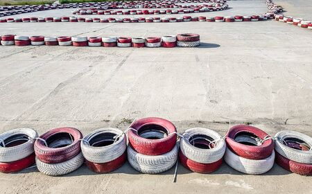 Racing track for go-karts with dividing lines made of painted and white car tires on asphalt.
