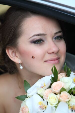 A bride with a bouquet in her hand and a ladybird on her cheek in a car in the back seat.