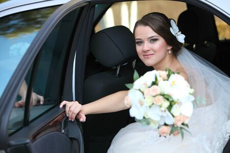 Cute bride with a bouquet in her hand in a car in the back seat Standard-Bild