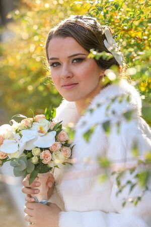 The bride in a white fur coat on a background of bushes holds a wedding bouquet in her hands.