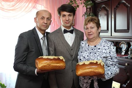 Portrait of a groom with his parents holding bread in their hands at home Stock Photo