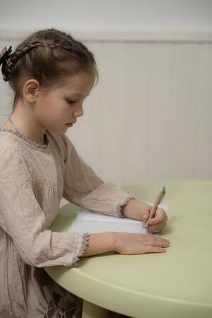 A dark blond girl in a beige dress is doing homework