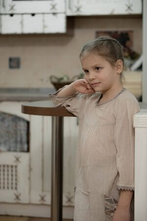 Dark blonde girl in a beige dress in the middle of the kitchen.