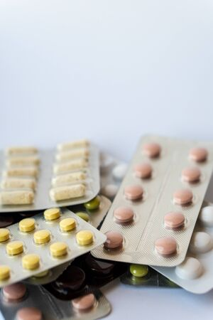 Medicine and pills. Multi-colored medicines on a white background close-up. Plate with multi-colored tablets on a white background. Multi-colored tablets that spilled from an inverted jar onto a white surface.