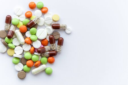 Medicines and pills. Multicolored medicines on a white background close-up. A slide of colored tablets on a white background. Multi-colored tablets that spilled from an inverted jar onto a white surface