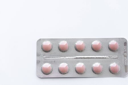 Medicines and pills. Multicolored medicines on a white background close-up. Plate with pink pills on a white background. Multi-colored tablets that spilled from an inverted jar onto a white surface.