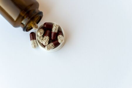 Medicine and pills. Medicines on a white background close-up. Brown glass bucket with capsules inside on a white background. Pills that spilled out of an inverted jar onto a white surface.