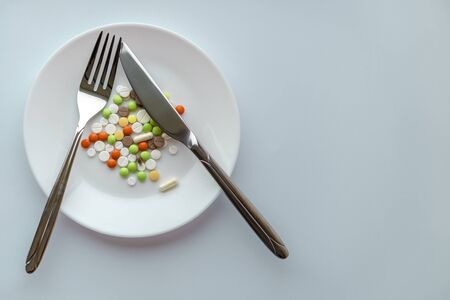 Pills on a white plate. Gesture with a knife and fork pause, on a plate with pills. Medicines on a white background. A pile of multi-colored tablets disguised as food on a plate with cutlery.