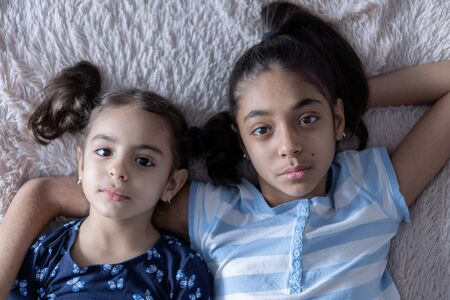 Two black young girls, sisters, lie in bed in an embrace on their backs. Persian girls on the bed with a phone. Middle Eastern children. Stock fotó
