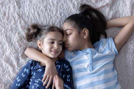 Two black young girls, sisters, lie in bed in an embrace on their backs. Persian girls on the bed with a phone. Middle Eastern children.