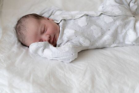 A newborn baby lies on his back with his eyes closed and covers his right eye with his hand in the first minutes of life. A newborn with traces of primordial lubrication is sleeping.