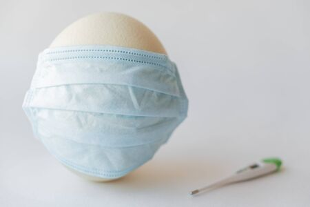Large white easter ostrich egg in a medical mask and a thermometer. Egg in a respirator and a thermometer. Easter and Coronavirus, Covid-19. Ostrich egg in a medical mask and a thermometer on a white background.