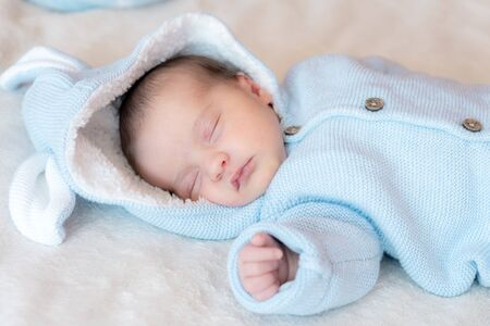 Primer plano del bebé recién nacido. Vista lateral de un bebé recién nacido durmiendo profundamente de espaldas con una blusa azul con capucha y orejas sobre un fondo blanco. Retrato de un bebé recién nacido durmiendo sobre un fondo beige.