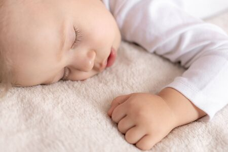 Childhood, sleep, rest, family, lifestyle concept - close-up portrait of a cute little boy of 2 years old in a white body sleeping on a beige bed at noon with mouth open top and side view.