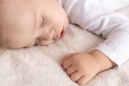 Kindheit, Schlaf, Ruhe, Familie, Lifestyle-Konzept - Nahaufnahme eines süßen kleinen Jungen von 2 Jahren in einem weißen Körper, der mittags auf einem beigen Bett mit offenem Mund und Seitenansicht schläft.