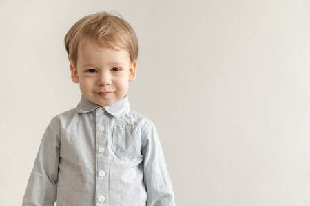 childhood, emotions concept - medium plan isolate little cute two-year-old blond-haired boy in a gray shirt shows grimaces on a white background copy space.