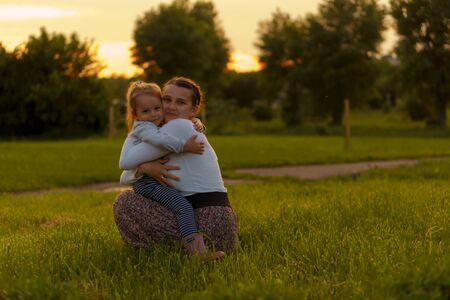 Motherhood, care, infants, summer, parenting concept - Young mom with with three year old little girl daughter in her arms walks and looks at child in backlight of sunset in park near flowering bush.