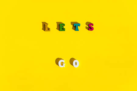 Flat lay of wood multicolored letters is inscription of lets go with shadow on bright plain yellow background. wishes and messages made up of models of alphabet: gifts, postcards, screensavers concept