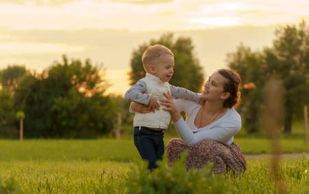 Motherhood, care, infants, summer, parenting concept - Young beautiful mom with son aged two years old have fun spend time outside in backlight of a sunset in the park near the flowering bush. Stockfoto