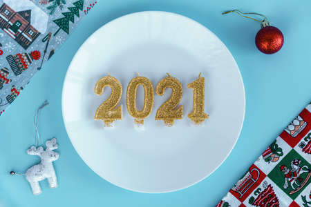 Xmas, winter, new year, festive table and treats, food concept - Blue Christmas background with white plate on which candles instead of dish in form of numbers 2021 with different accessories. Flatly Standard-Bild