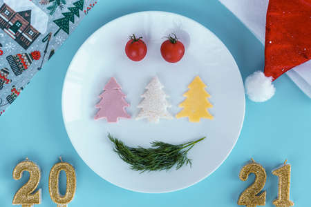 Xmas, winter, new year, festive table and treats, food concept - Blue background with plate with different products in shape of Christmas tree 2021 number candles santa hat. Flatly, top view, overhead