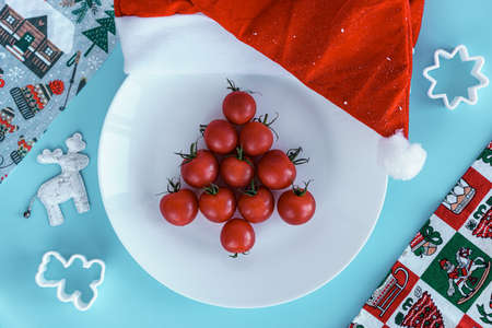 Xmas, winter, new year, festive table and treats, food concept - Blue background with plate with christmas tree lined with red cherry tomatoes 2021 number candles santa hat. Flatly, top view, overhead Standard-Bild