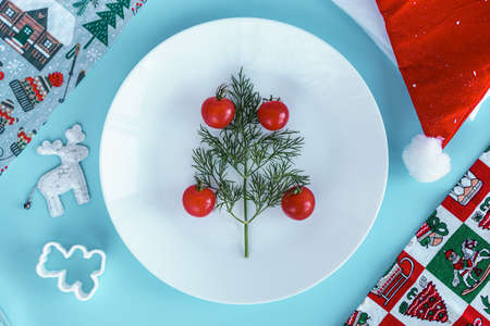 Xmas, winter, new year, festive table and treats, food concept - Blue background with dill branch Christmas tree with cherry tomatoes instead of decorations on plate santa hat. Flatly, overhead