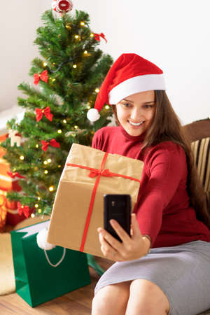 soft focus. cute girl in Santa hat remotely wishes happy holiday videoconference via smartphone online hold gift box sitting near Christmas tree- Xmas, winter, new year, Celebration, family concept