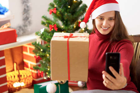 Xmas, winter, new year, Celebration, family concept - cute girl in Santa hat remotely wishes happy holiday videoconference via smartphone online hold gift box sitting near Christmas tree in quarantine Standard-Bild