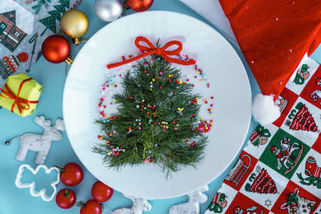 Xmas, winter, new year concept - layout white plate on which there are Christmas tree dill tree decorated with multicolored small balls with santa hat and bakeware on Blue background.