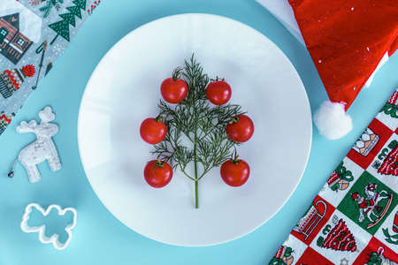 Xmas, winter, new year concept - layout white plate on which there are Christmas tree dill tree decorated with red cherry tomatoes in a triangle shape with santa hat and bakeware on Blue background.