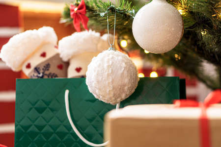 Xmas, winter, new year, Celebration, family, gift concept - Holiday atmosphere at home. Bright presents boxes under Christmas tree decorated with balls on background red fireplace with burning fire Standard-Bild