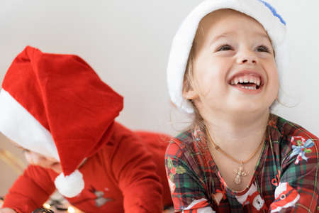 merry xmas and happy new year, infants, childhood, holidays concept - close-up 6 month newborn baby in santa claus hat and red bodysuit with elder sister play with decorations balls on christmas tree
