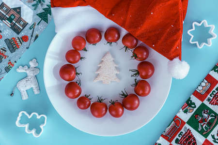Xmas, winter, new year concept - layout white plate on which there are Christmas tree carved from bread and surrounded red cherry tomatoes with santa hat and bakeware on Blue background Standard-Bild