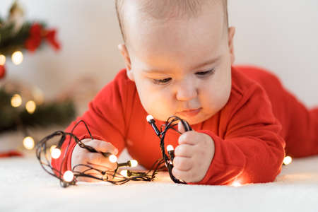 merry christmas and happy new year, infants, childhood, holidays concept - close-up 6 month old newborn baby in red clothes on his tummy crawls with decorations, lights gerlandy on christmas tree. Standard-Bild