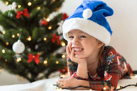 merry xmas and happy new year, childhood, holidays concept - close-up little smiling girl in blue santa claus hat on his tummy play and have fun on bed with decorationsand lights on christmas tree.